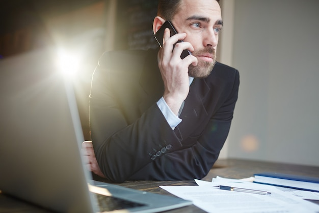 Successful businessman calling by phone while working
