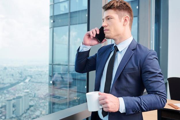 Успешный бизнесмен, звонящий по телефону