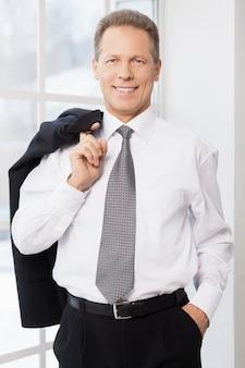 성공적인 사업가입니다. 셔츠와 넥타이를 입은 쾌활한 성숙한 남자가 재킷을 손가락으로 잡고 창 근처에 서 있는 동안 카메라를 보며 웃고 있다