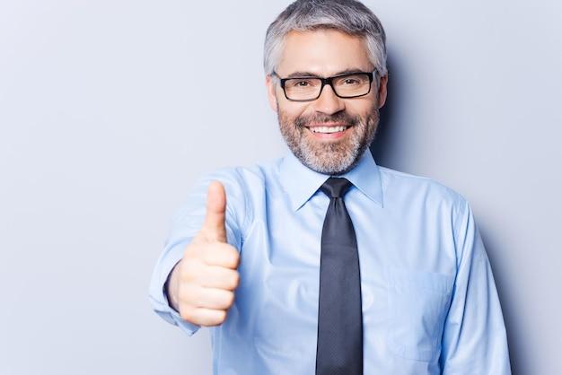 성공적인 사업가입니다. 셔츠와 넥타이를 매고 카메라를 바라보고 회색 배경에 서서 엄지손가락을 치켜드는 쾌활한 성숙한 남자
