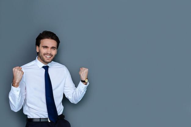 성공적인 사업가. 성공적인 거래를하면서 웃고 자신의 감정을 표현하는 쾌활한 긍정적 인 좋은 사람