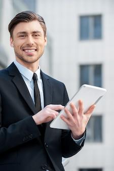 Успешный бизнесмен. веселые молодые люди в формальной одежде держат цифровой планшет и смотрят в камеру