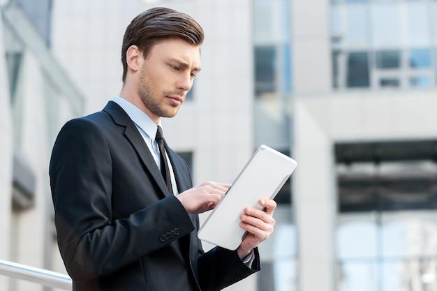 Успешный бизнесмен. веселые молодые люди в формальной одежде держат цифровой планшет