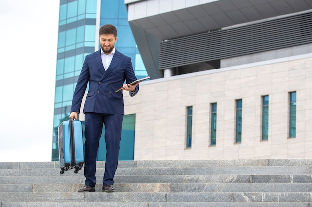 Successful businessman descends the steps against the background of the office business center
