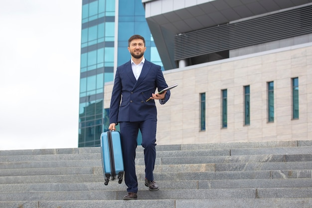 Successful businessman descends the steps against the office business center