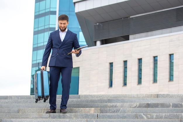 성공적인 사업가는 사무실 비즈니스 센터를 배경으로 계단을 내려갑니다.