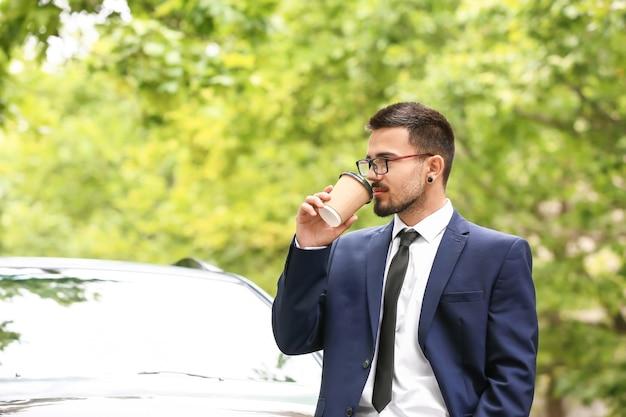 현대 자동차 근처에서 커피를 마시는 성공적인 사업가
