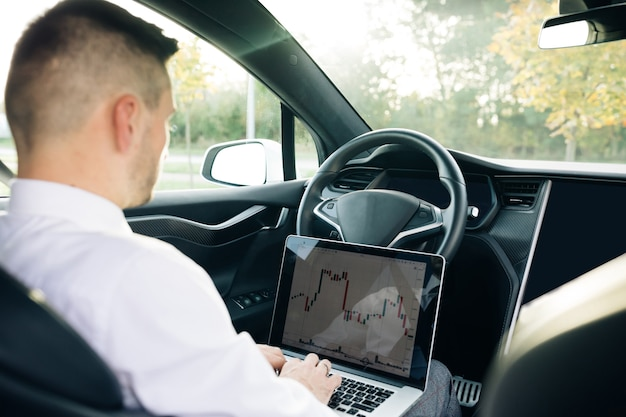Successful businessman in formal outfit opening personal laptop while sitting in modern car