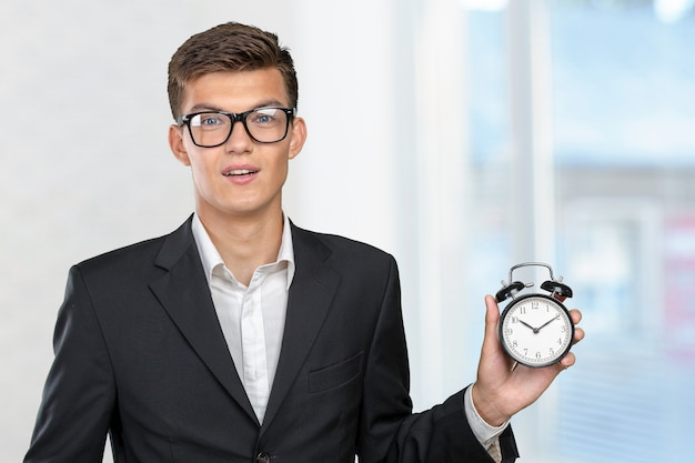 Successful businessman in formal wear pointing at clock
