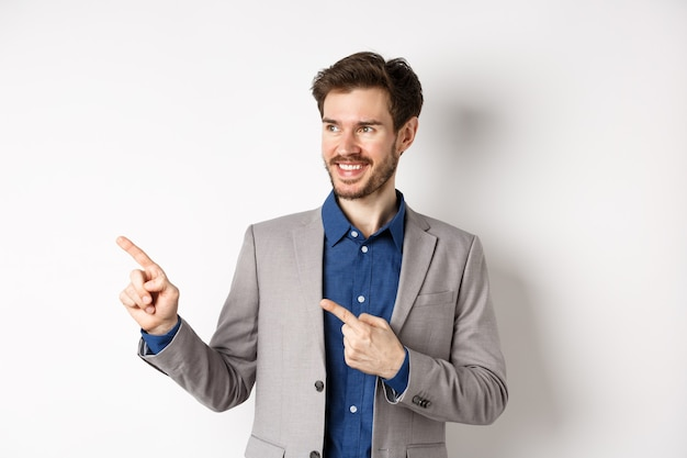 Successful businessman in grey suit pointing fingers left and looking at banner, smiling confident, showing advertisement, standing against white background.