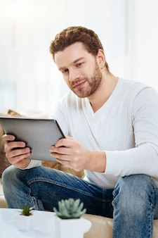 Successful businessman. handsome cheerful pleasant man holding a tablet and working on it while sitting in his office
