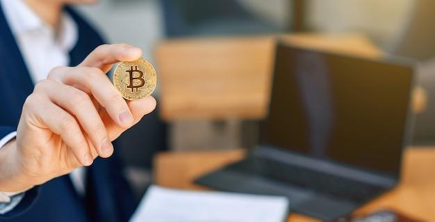 成功した実業家は彼の手に金のビットコインコインを持っています。暗号通貨のビジネスコンセプト
