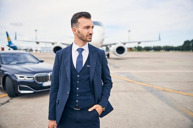 黒い車のそばの飛行機の前に立っているエレガントなスーツで成功した実業家