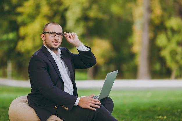 白いシャツ、古典的なスーツ、正しい眼鏡で成功した実業家。男は柔らかいプーフに座って、自然の屋外の緑の芝生の都市公園でラップトップpcコンピューターで作業します。モバイルオフィス、ビジネスコンセプト。