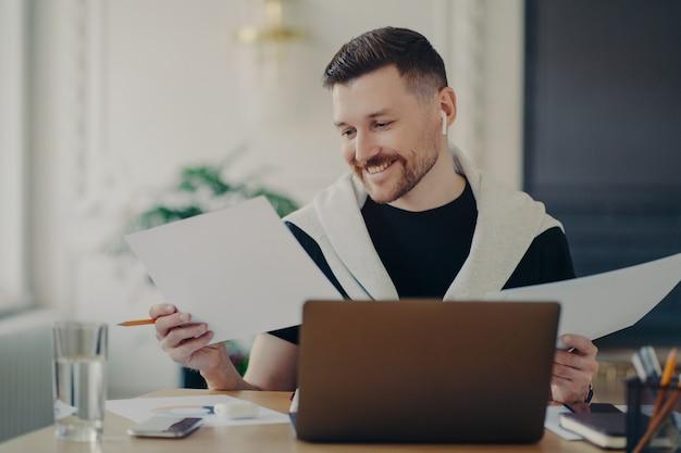 自宅で仕事をしながら、ドキュメントを分析し、業績に満足しているように見える、ワイヤレスイヤホンで成功したビジネスマン。職場に座って幸せを感じている男性サラリーマン