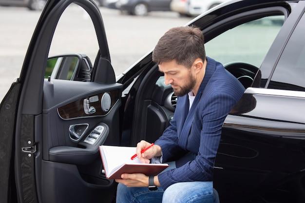 성공적인 사업가는 그의 권위있는 차 근처에 앉아있는 동안 문서에 종사하고 있습니다.