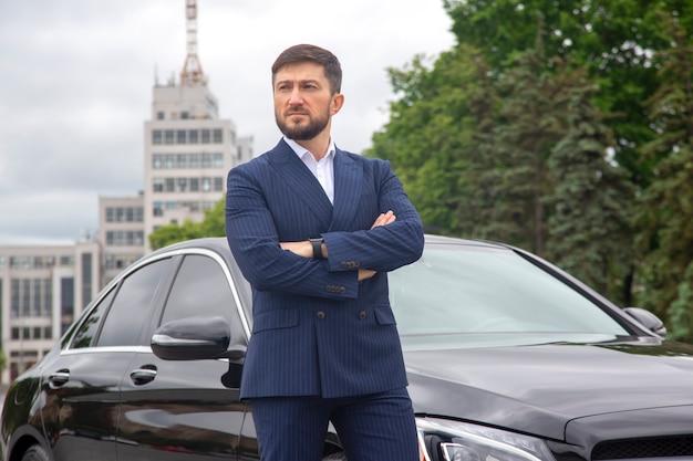 성공적인 사업가 그의 권위있는 차 근처에 서