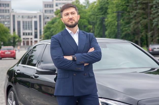 성공한 사업가가 그의 권위 있는 차 근처에 서 있다