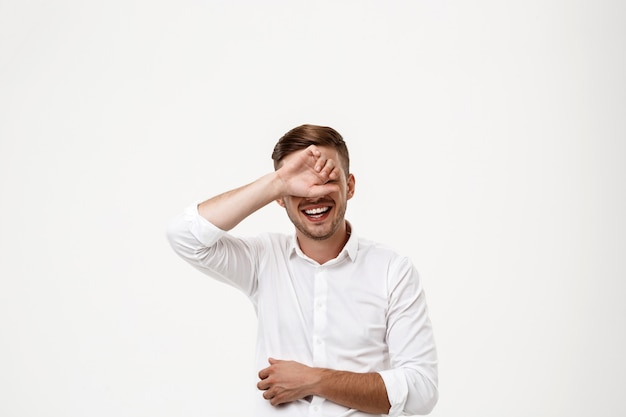Successful businessman laughing, hiding eyes behind hand.