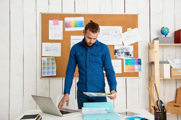 ラップトップで職場に座って、論文を見て成功した実業家