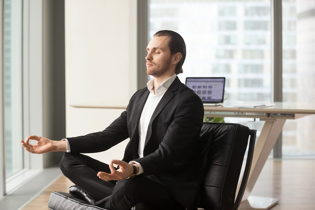 Successful businessman meditating at workplace