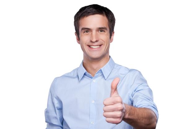 成功した実業家。白いシャツに孤立して立っている間彼の親指を上げて笑っている青いシャツを着たハンサムな若い男の肖像画