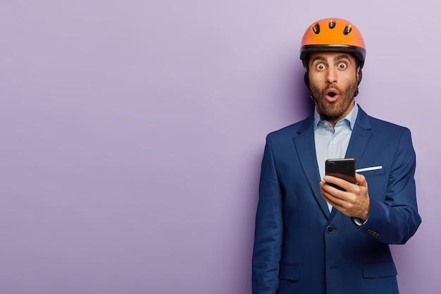 上品なスーツとオフィスで赤いヘルメットでポーズをとって成功した実業家