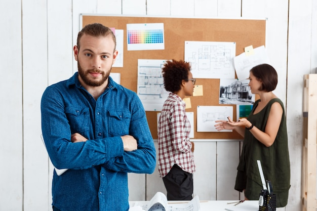 成功した実業家が組んだ腕でポーズ同僚の背景にアイデアを議論します。