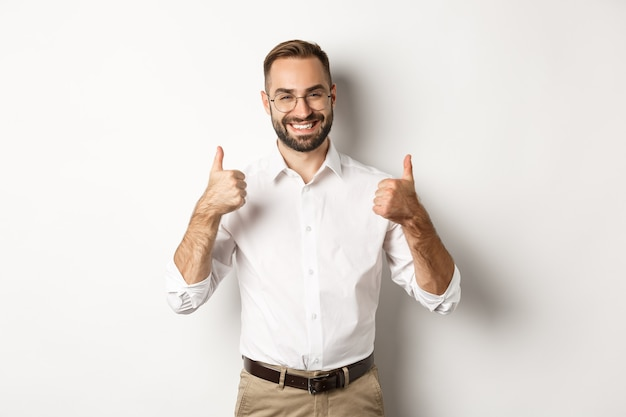 Successful businessman praising good work, showing thumbs up and smiling satisfied, standing over white background.