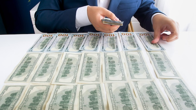 Successful businessman putting money on office desk while counting them
