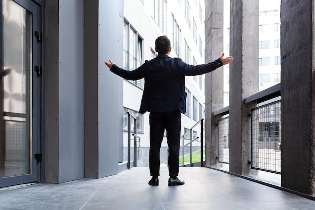 成功した実業家は、現代のオフィスの背面図の近くで勝利と成功の兆候を上げます