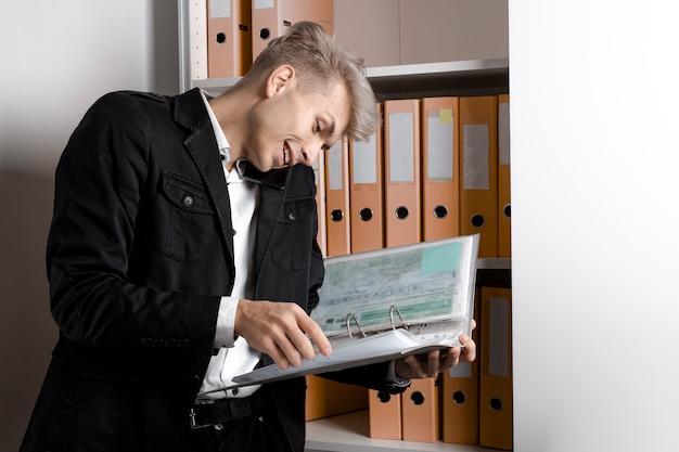 Успешный бизнесмен читает документы и разговаривает по телефону в офисе