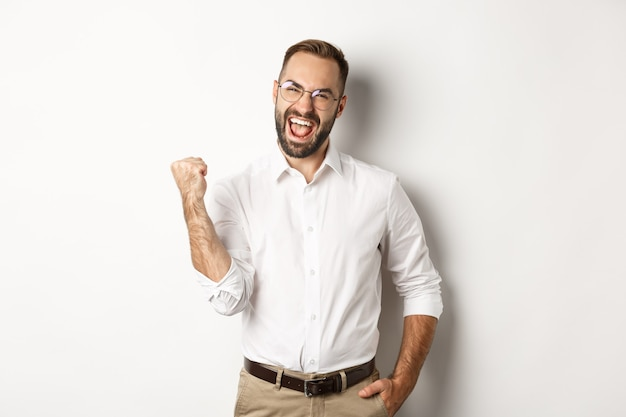 Successful businessman rejoicing, making fist pump and saying yes, achieve goal, standing over white background.