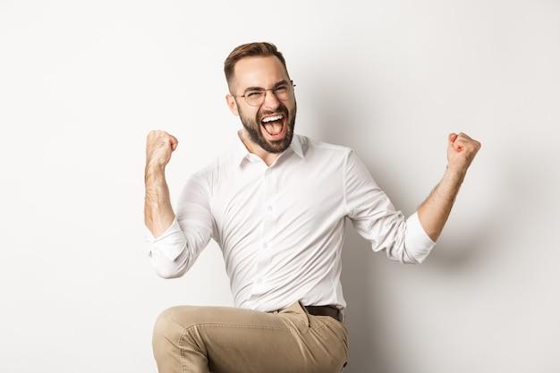 成功した実業家は喜び、手を上げて勝利を祝い、何かを勝ち取る