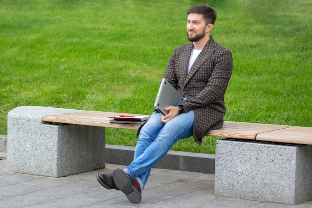 Successful businessman resting on a city bench after a completed work project
