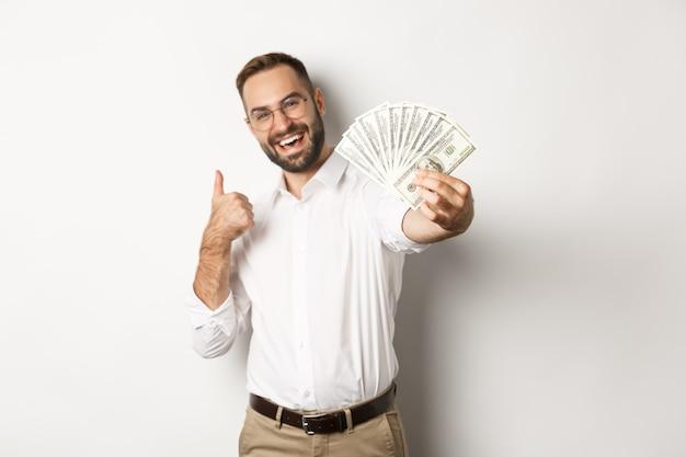 成功したビジネスマンは、白い背景の上に立って、満足のいく笑顔で、お金のドルと親指を示しています。コピースペース