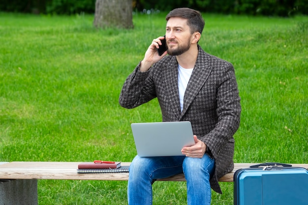 Successful businessman sits on a city bench and is engaged in business with documents and laptop