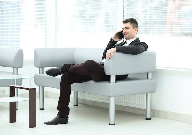 Successful businessman sits in the lobby of the office and talking on a smartphone
