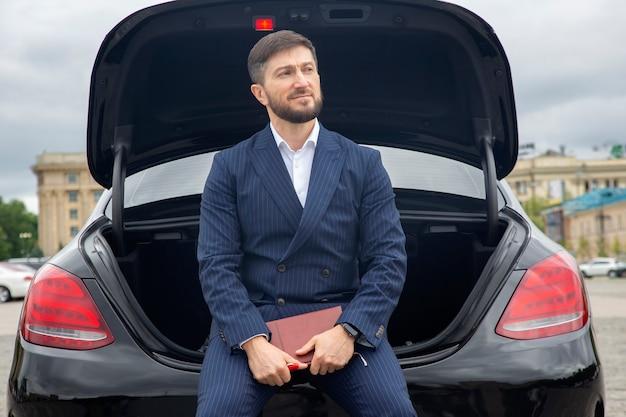 성공한 사업가는 그의 유명한 자동차 후드에 일기장을 얹고 앉아 있다