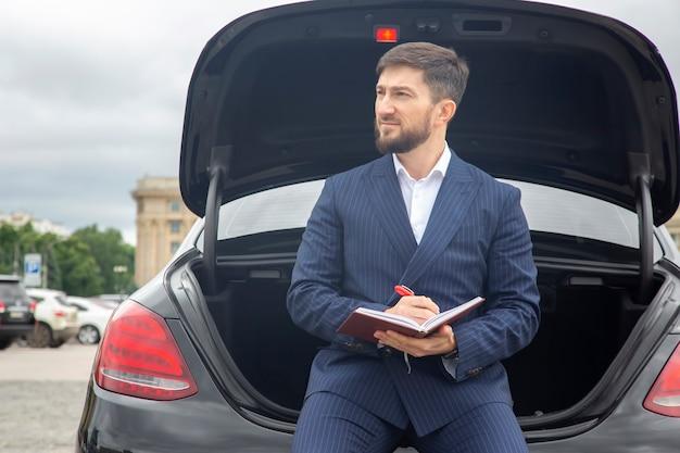 성공한 사업가는 그의 유명한 자동차 후드에 일기장을 얹고 앉아 있다 프리미엄 사진