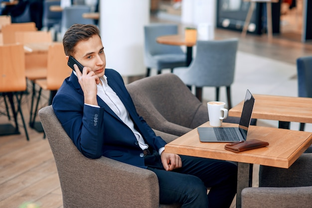 Successful businessman speaking on smartphone on his workplace with laptop, wallet and notebook