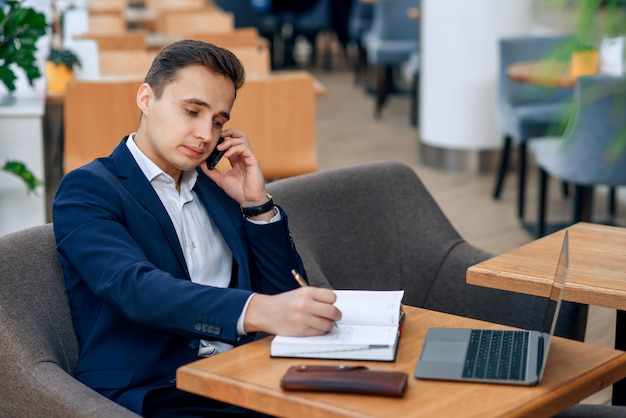 Successful businessman speaking on smartphone and making notes