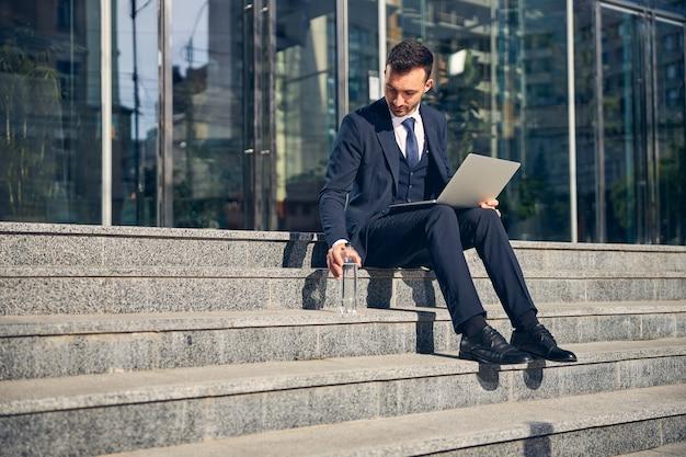水のボトルを飲みながら、ラップトップを膝に乗せて階段で時間を過ごす成功したビジネスマン