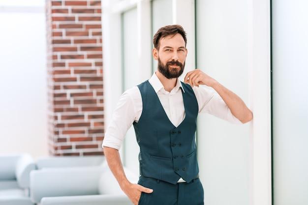 Успешный бизнесмен, стоя в современном офисе.