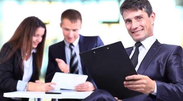Successful businessman standing with his staff in the background at office