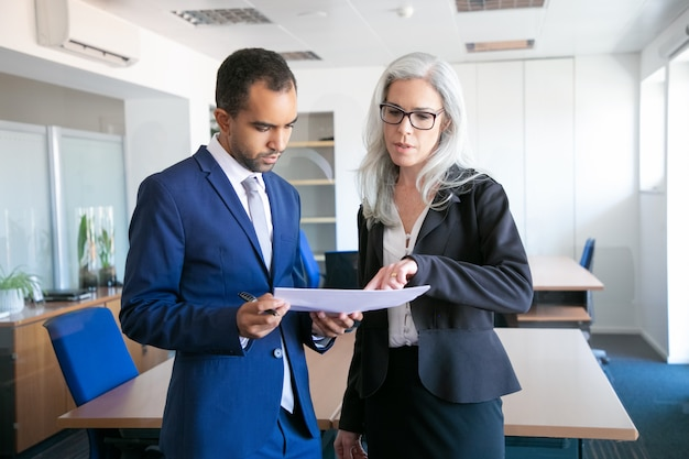 Successful businessman in suit reading document for signing and female grey-haired manager in eyeglasses pointing at something in report. partners working in office. business and management concept