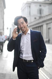 Успешный бизнесмен разговаривает по телефону во время прогулки по улице