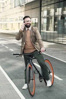 Успешный бизнесмен разговаривает по мобильному телефону во время езды на велосипеде по городу