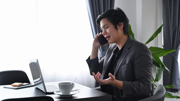 Успешный бизнесмен разговаривает по мобильному телефону, сидя в современном офисе.