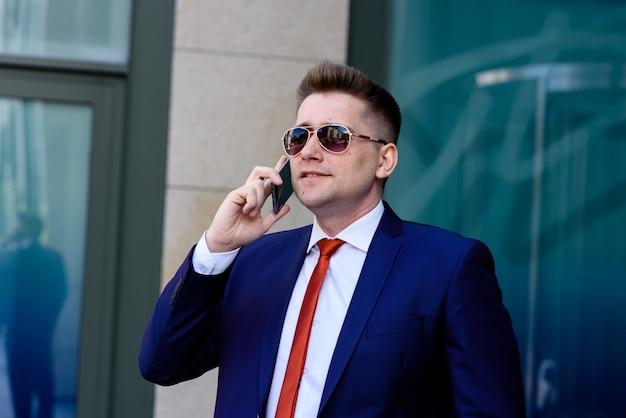 電話で話し、笑顔で成功した実業家。